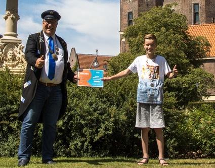 Tobias uit Zwolle ontvangt prijzenpakket uit handen van Peter Vader (Foto Klaas Bootsma)